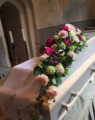 Snett över kistan går denna cerise, rosa, lila dekoration