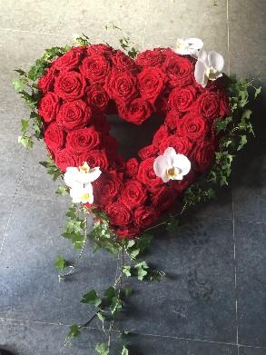 Öppet hjärta med röda rosor och orkidéer