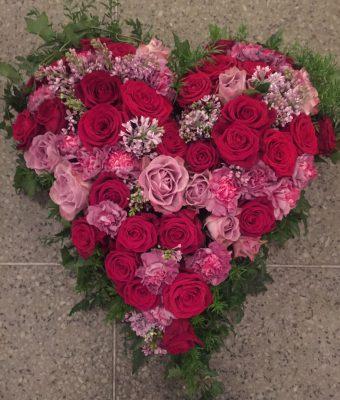 Fyllt hjärta med årstidens mixade blommor i lila och cerise