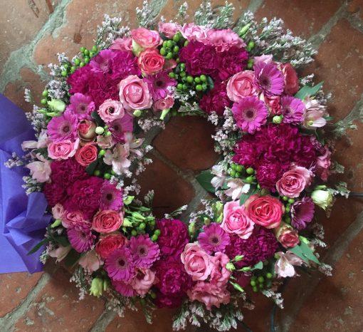 Urnkrans / Rundbunden krans i årstidens mixade blommor i cerise och rosa