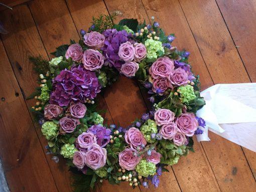 Urnkrans / Rundbunden krans i årstidens mixade blommor i lila och lime
